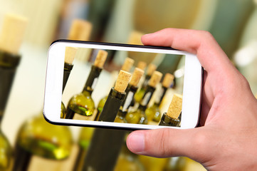 Hands taking photo wine bottles with smartphone