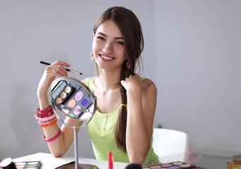 Young beautiful woman making make-up near mirror,sitting at the