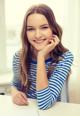 smiling teenage girl with notebook at home