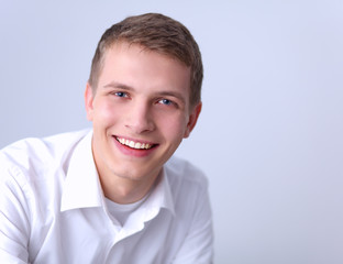 Portrait of young man smiling sitting on gray background
