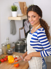 Young woman cutting vegetables in kitchen, standing near desk