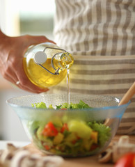 Smiling young woman  mixing fresh salad, holding bottle of oil