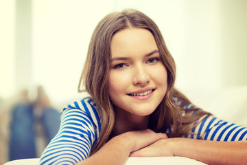 smiling teenage girl lying on sofa at home