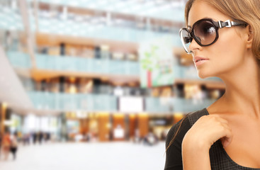 beautiful woman in shades over mall background