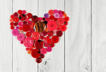 Heart shape of red and pink buttons over white wood background