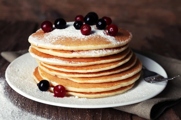 Stack of delicious pancakes with powdered sugar and berries