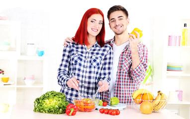 Happy couple preparing  vegetable salad in kitchen