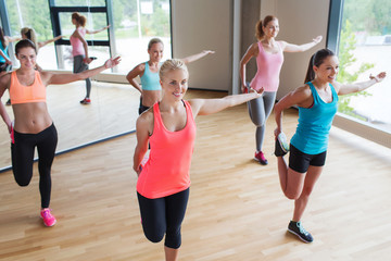 group of women stretching leg in gym