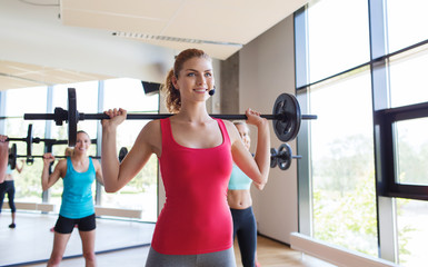 group of women excercising with bars in gym