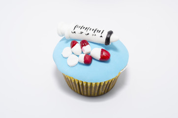 Cupcake with medical equipment and medicines made of fondant