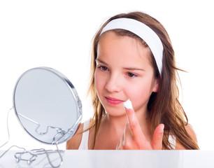 Teenage girl creaming her face