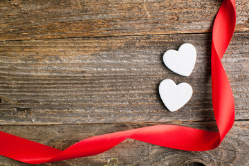 White glitter hearts with red satin ribbon on reclaimed wood, va