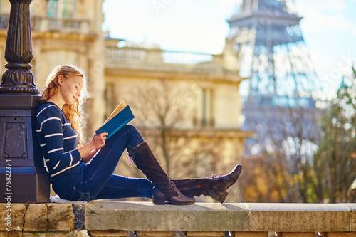 Beautiful woman in Paris, reading a book - 75822374