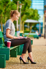 Business woman working on her laptop outdoors