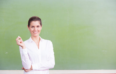 Happy female teacher holding chalk smiling to the classroom in f