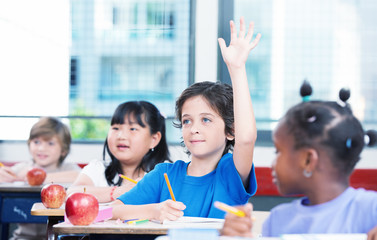 Multiracial classroom primary school. Kid raising his hand ready