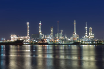 Oil refinery at twilight with river reflexion