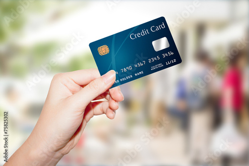 female hand holding credit card - 75825302