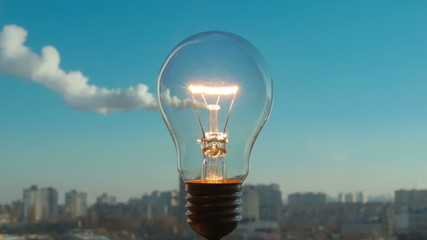 The incandescence bulb by the industrial city background