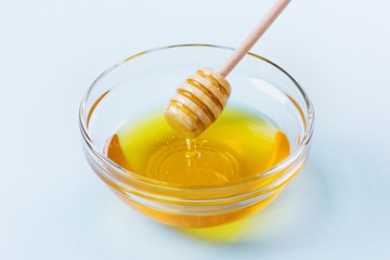 honey drip from a wooden honey dipper in glass bowl