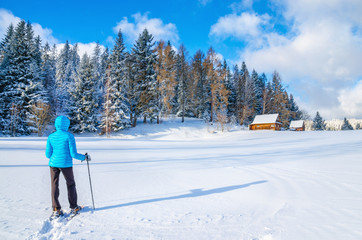 Young woman in blue down jacket walking towards remote mountain