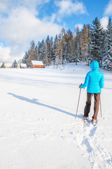 Young woman walking with snow shoes on fresh snow wood house