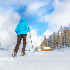 Young woman running with snow shoes on clear snow and remote cot