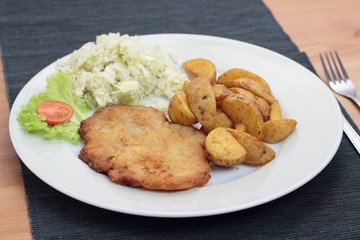 Wiener schnitzel with fried potato wedges and cabbage salad.