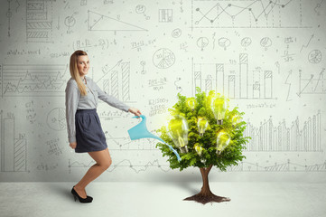 Business woman pouring water on lightbulb growing tree