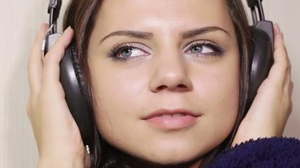 Girl bathrobe in headphones CU
