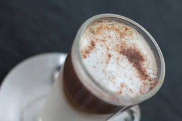 Closeup of cafe latte sprinkled with cocoa.