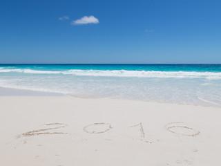 2016 inscription on the white sand