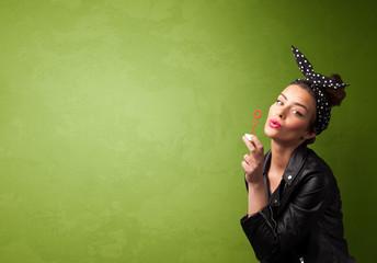 Beautiful woman blowing soap bubble on copyspace background