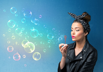Pretty lady blowing colorful bubbles on blue background