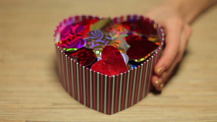 Woman's hands open box with present for Valentine's Day