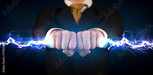 canvas print picture Business man holding electricity light bolt in his hands