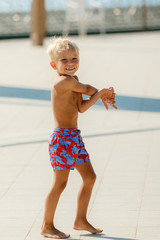 Boy playing with ball on summer playground