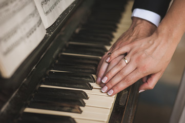 hands with wedding rings on piano