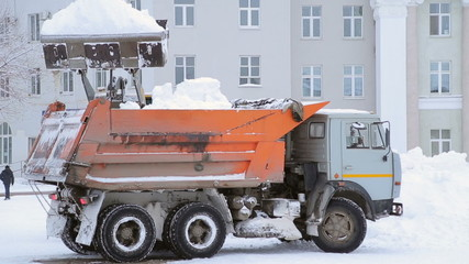 Snow removal in the winter, excavator bucket dumps of snow in th