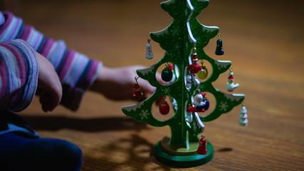 Boy's hand decorating Christmas tree toy