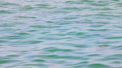 Red float on  sea water surface  background  with small  waves