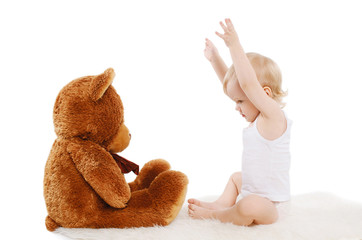 Baby playing with teddy bear toy