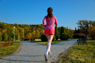 Woman running in autumn park, girl runner jogging