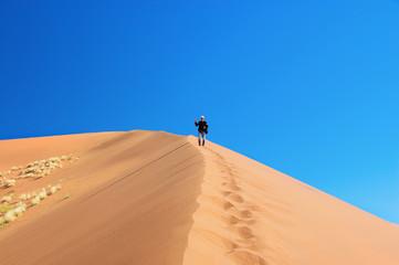 Man on dunes of Namib desert, Namibia, South Africa