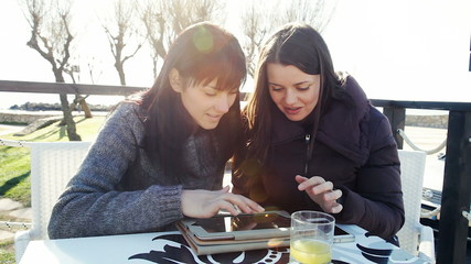 Happy girlfriends outdoors having fun with tablet