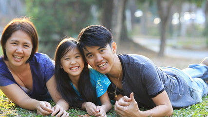 Happy Asian family playing together in park