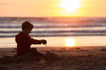 Adorable kid, playing on the beach on sunset time