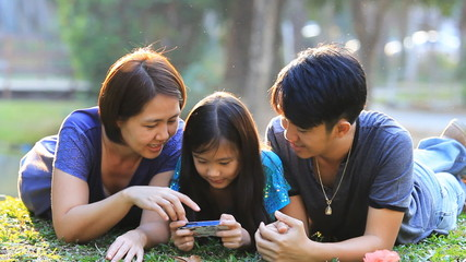 Happy Asian family playing game in smart phone together