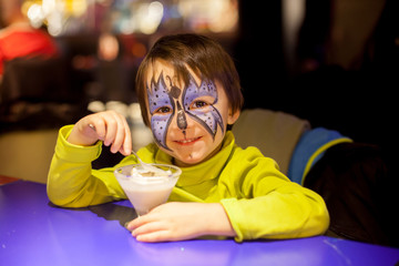 Little boy with painted face as butterfly, eating ice cream