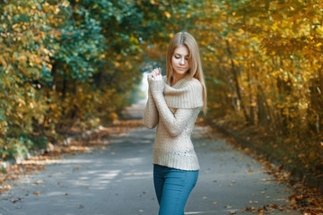 Cute woman in a jersey standing in autumn park